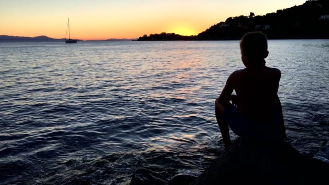Admiring sunset. Boy sitting on a rocky beach looking at view
