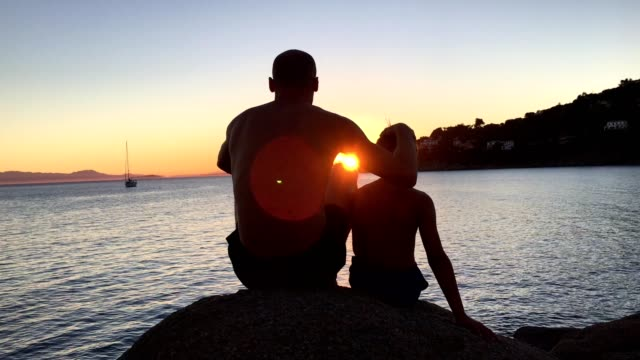 Admiring sunset. Father and son sitting on a rocky beach looking at view