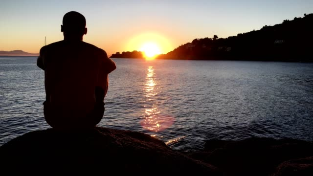 admiring sunset. man sitting on a rocky beach looking at view - outline stock videos & royalty-free footage