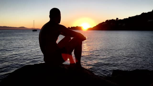 Admiring sunset. Man sitting on a rocky beach looking at view