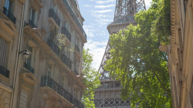 vídeos de stock e filmes b-roll de admiring the majestic eiffel tower from inbetween parisian buildings - cultura francesa