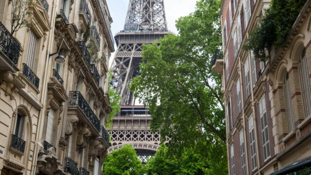 admiring the majestic eiffel tower from inbetween parisian buildings - eiffel tower stock videos & royalty-free footage