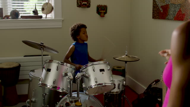 stockvideo's en b-roll-footage met adolescent boy plays drums at home - drummer
