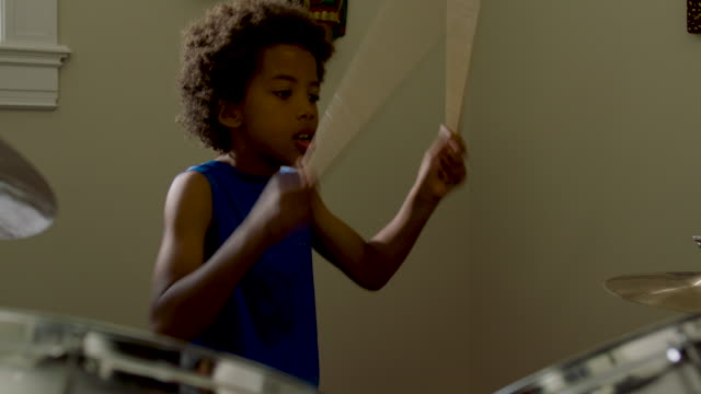 stockvideo's en b-roll-footage met adolescent boy plays drums at home - drummer