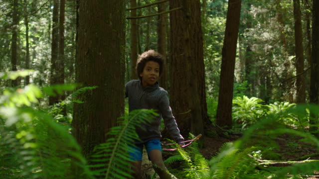 Adolescent boy shoots toy bow and arrow in a forest