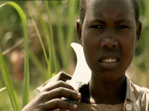 cu adolescent boy with machete on shoulder / kigali, rwanda - フツ族点の映像素材/bロール