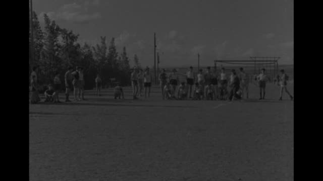 adolescent boys playing ball, running foot-races / blond boy / boys and girls practicing shot put moves / four boys shinny up pipes and drop / husky... - shot put stock videos & royalty-free footage