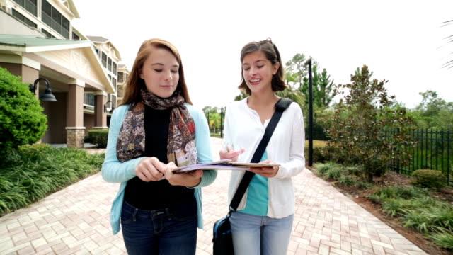 Adolescent weibliche Studenten Hausaufgaben Aufgabe, während walking im Freien