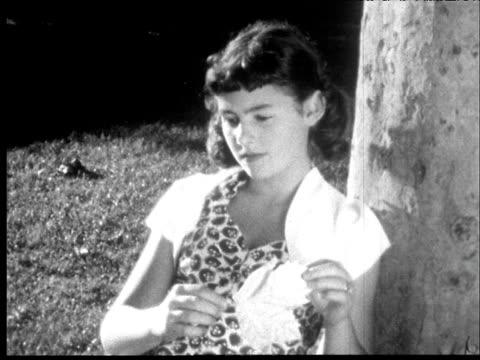 1953 B/W Adolescent girl sits against tree and twirls leaf