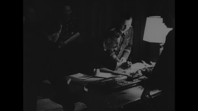 adolf hitler and benito mussolini inside the fuhrerbau during munich conference / hitler bent over desk having just signed munich agreement document... - adolf hitler stock videos & royalty-free footage