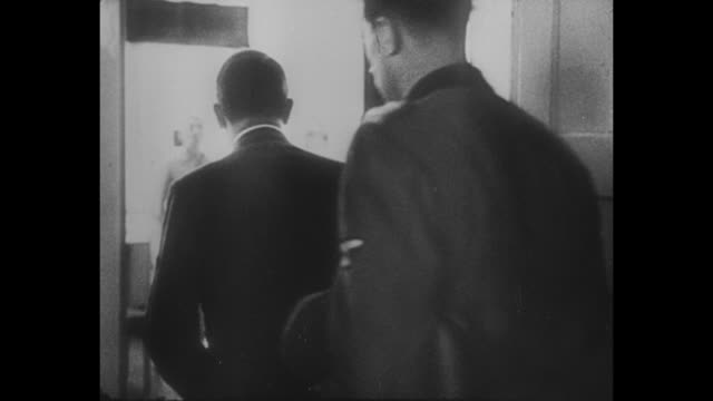 Adolf Hitler and entourage approach walking in hospital hall then turn to walk into room / Hitler walks along row of hospital beds containing wounded...