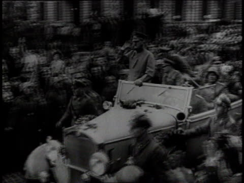 vidéos et rushes de adolf hitler and his entourage riding cars past cheering people / crowd in street behind cars - 1939