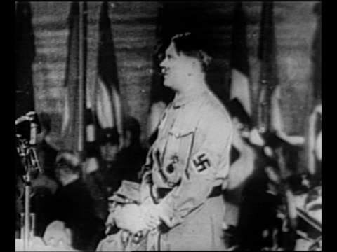 vídeos de stock, filmes e b-roll de adolf hitler, in brown shirt and nazi armband, makes his first speech as chancellor at the sportpalast in berlin; bank of nazi flags stands behind... - adolf hitler
