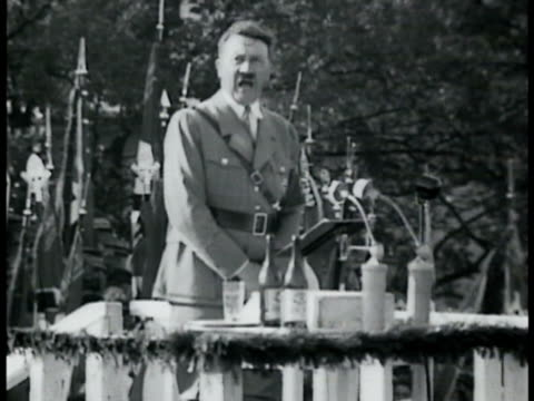 stockvideo's en b-roll-footage met adolf hitler in nazi uniform walking w/ hemann goering huge crowd saluting hitler giving short speech on podium huge saluting crowd. night: crowd... - 1935