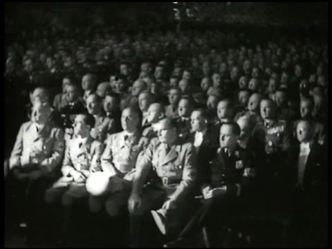 Adolf Hitler in uniform standing behind podium speaking large seated crowd of soldiers Nazi flag fading up over Hitler
