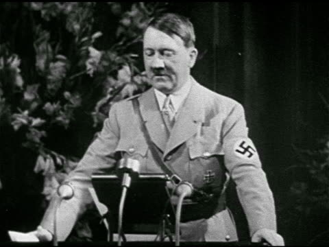 stockvideo's en b-roll-footage met adolf hitler in uniform, standing behind podium speaking , large seated crowd of soldiers. nazi flag waving in wind. - 1935