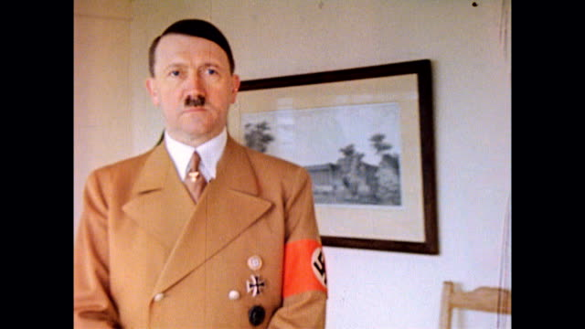 vídeos de stock, filmes e b-roll de adolf hitler indoors at his berghof estate, wearing brown suit with nazi swastika arm band / interior view of a massive window in the great room of... - adolf hitler
