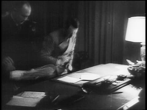 adolf hitler leaning over desk signing documents / munich pact - anno 1938 video stock e b–roll
