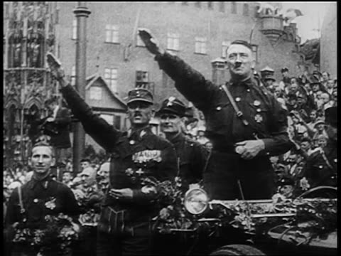 vídeos de stock, filmes e b-roll de adolf hitler + other nazi officers giving fascist salute at nuremberg rally / newsreel - adolf hitler