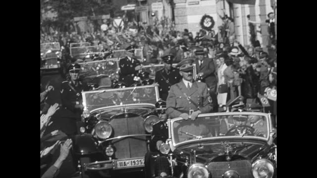 VS Adolf Hitler reviews troops / he stands in rear of open car receiving a rapturous welcome from Bad Godesberg citizens waving small flags meeting...