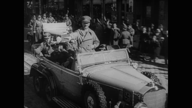 vídeos de stock, filmes e b-roll de adolf hitler rides into vienna triumphant during the invasion of austria in march of 1938 before an animated nazi swastika drips onto a european map,... - adolf hitler