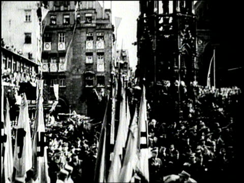 stockvideo's en b-roll-footage met adolf hitler salutes german soldiers carrying nazi flags as they march past in a parade. - 1936