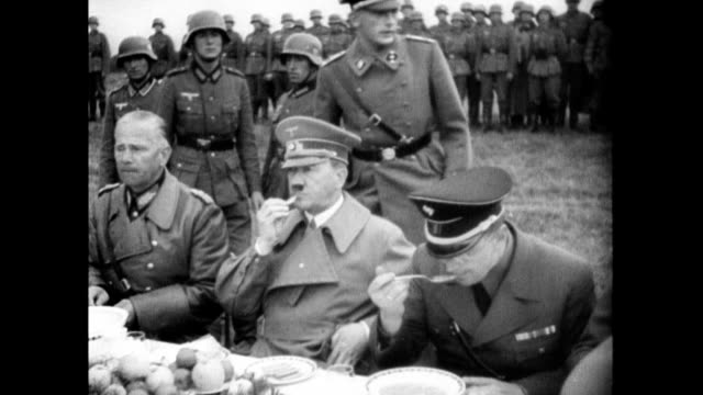 / adolf hitler sitting down to eat outdoors with other nazi officers / soldiers serving food hitler eating with his fingers** nazis eating outdoors... - anno 1938 video stock e b–roll
