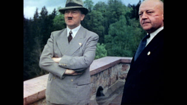 Adolf Hitler talking with officials on the terrace of Berghof Hitler wearing suit and hat / Eva Braun's sister Gretl Braun with German diplomat...