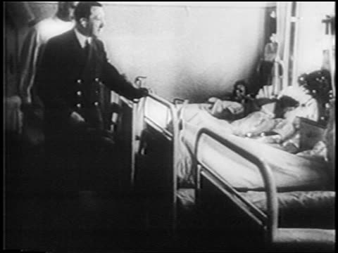 vidéos et rushes de adolf hitler visiting patients in hospital / newsreel - 1945