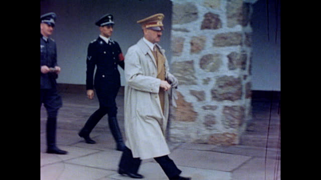 vídeos de stock, filmes e b-roll de adolf hitler walking out of berghof with nazi officers / hitler puts on gloves as he walks and wears a raincoat and military hat / hitler walks down... - adolf hitler