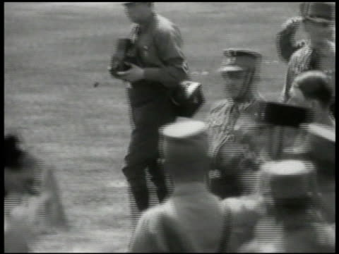 hitler adolf hitler walking w/ male in uniform walking through men in sa uniforms swastika arm bands some holding small flags saluting w/ raised arm... - braun stock-videos und b-roll-filmmaterial
