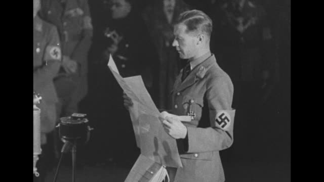 Adolf Hitler walks onto stage in room surrounded by members of Nazi party he gives them Nazi salute / man in Nazi uniform stands in front of stage...