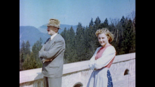 vídeos de stock, filmes e b-roll de adolf hitler, wearing suit and hat, looks at a document on the terrace of berghof / chief aide julius schaub, nazi official adolf wagner and personal... - adolf hitler