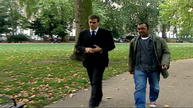 clash of cultures england london ext damon green walking through park with nick pendry and both sit on bench - damon green stock videos and b-roll footage