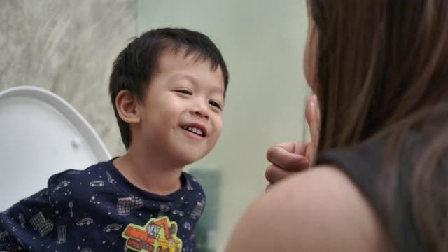vídeos de stock, filmes e b-roll de adorável menino asiático sentado no vaso sanitário em casa com a mãe pela manhã. conceito de cuidados de saúde.bebê de 3 anos. - bebês meninos