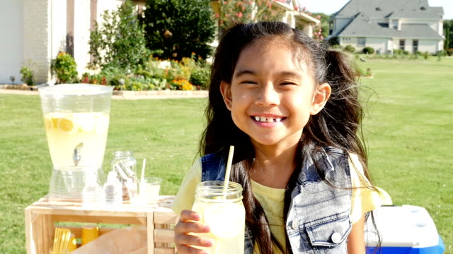 adorable asian little girl smiling in front of lemonade stand - selling stock videos & royalty-free footage
