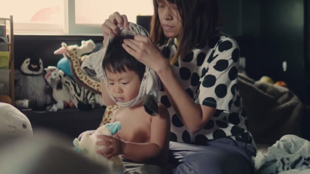 asian mother changing clothes to her baby boy on bed - young family stock videos & royalty-free footage