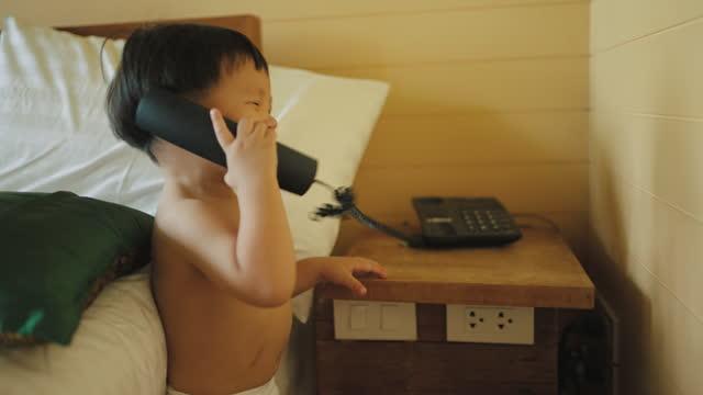 電話で呼び出す愛らしい男の子 - 受話器点の映像素材/bロール
