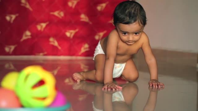 Adorable baby boy crawling on floor