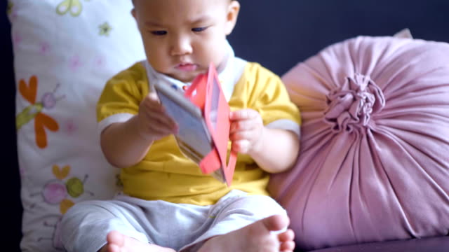 adorable baby boy playing mobile phone - baby boys stock videos & royalty-free footage