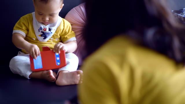 stockvideo's en b-roll-footage met schattig baby boy spelen van mobiele telefoon - generation z