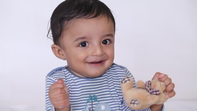 adorable baby boy playing with teddy bear - ぬいぐるみ点の映像素材/bロール