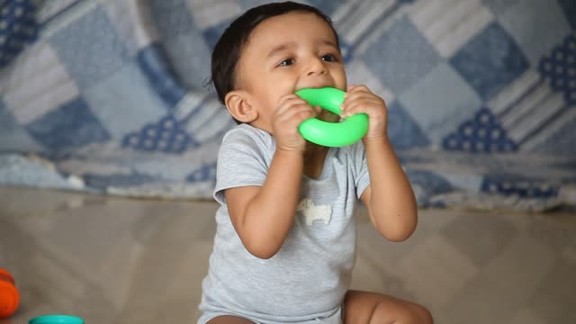 Adorable baby boy playing with toy on floor