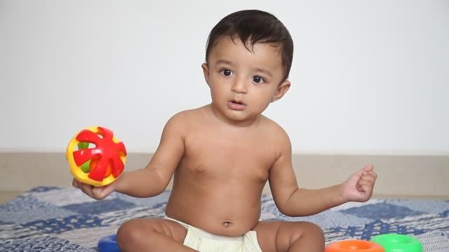 vídeos de stock, filmes e b-roll de adorable baby boy playing with toy rattle on floor - só um bebê menino