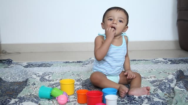 Adorable baby boy playing with toy rattle on floor
