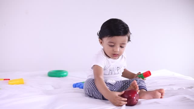 adorable baby boy playing with toy rattle on floor - babies only stock videos & royalty-free footage