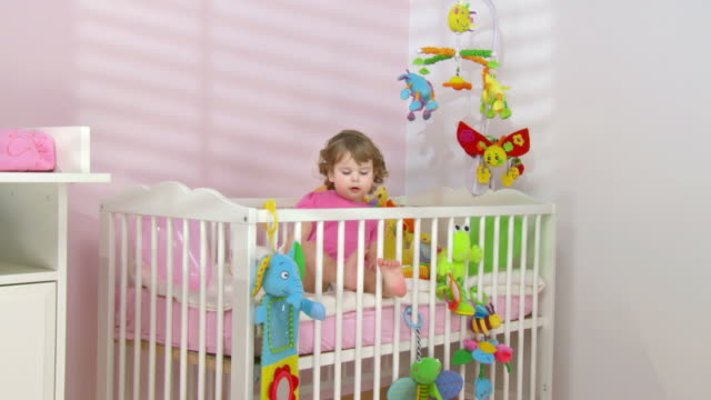 hd crane: adorable baby exploring the crib - crane shot stock videos & royalty-free footage
