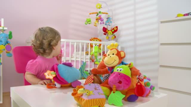 vídeos de stock, filmes e b-roll de grou hd: adorável menina bebê brincando com brinquedos - animal de brinquedo
