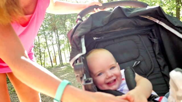 Hübsche Mutter und baby-Lachen beim Reiten in Kinderwagen im park