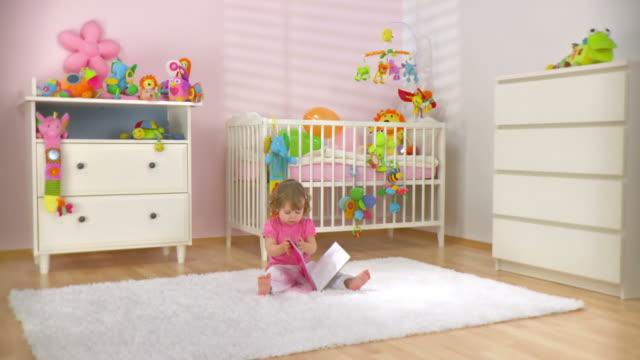 vídeos de stock, filmes e b-roll de hd dolly: adorável bebê com um livro - animal de brinquedo